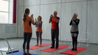 PAN of female yoga instructor standing before group of cheerful senior people: they are doing clapping exercise while warming up before class