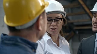PAN with slowmo of female construction coordinator in glasses and hard hat gesturing and explaining something to cheerful Asian businessman and unrecognizable male worker