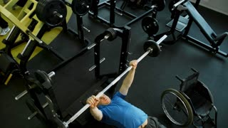 Crane shot of determined paraplegic man lying on bench and doing chest press in gym; empty wheelchair standing beside
