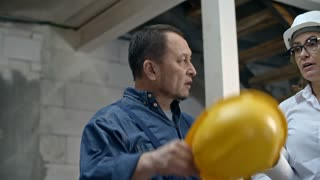 PAN with slowmo of female construction supervisor holding blueprints and explaining something to mature builder in hard hat