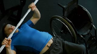 High angle shot with PAN of determined handicapped man lying on bench and doing chest press exercise with barbell in gym; empty wheelchair standing beside