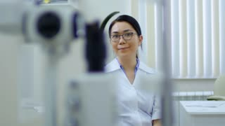 Tracking shot of smiling female eye care professional sitting and looking at camera in ophthalmology clinic
