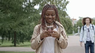 Teenage African girl in earphones smiling and texting to somebody on smartphone while walking in park
