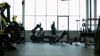 PAN with rear view of paraplegic man in wheelchair riding though gym with exercise machines and free weights
