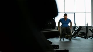 PAN of paraplegic man riding in wheelchair through gym with machines and free weights