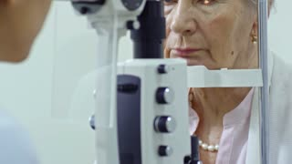 Tilt up of elderly woman looking at female optometrist while she examining her eye with slit lamp