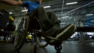 Low angle shot with tilt up of paraplegic man in wheelchair doing lateral raises with dumbbells in gym