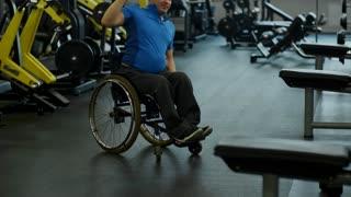 Tilt up of determined paraplegic man in wheelchair doing kettlebell shoulder press exercise in gym