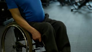 Tilt up of determined handicapped man sitting in wheelchair and shoulder press exercise with dumbbell in gym
