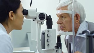 Panning shot of female ophthalmologist doing eye exam with slit lamp while checking eyesight of elderly man