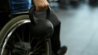 Tracking shot with rear view of unrecognizable paraplegic man in wheelchair doing one-arm rows with kettlebell