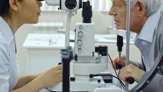 Tilt up of female doctor looking through binocular of slit lamp while examining eyes of senior man in ophthalmology clinic