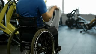 Tilt up with rear view of paraplegic man in wheelchair throwing towel over his shoulder and drinking from sports water bottle after workout in gym, then riding away