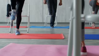 PAN with low-section of unrecognizable female fitness trainer standing on yoga mat and doing one-leg raises with group of elderly people using folding chairs for support