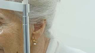 Close-up tracking shot of senior woman having an eye exam with slit lamp at ophthalmology clinic