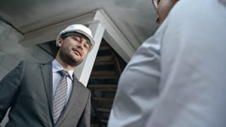 Tilt down of Asian construction engineer wearing suit and hard hat holding clipboard with layout plan and shaking hands with unrecognizable businesswoman