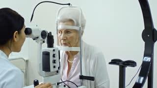 Female eye doctor using split lamp while examining eyes of senior lady and then explaining something on digital tablet screen