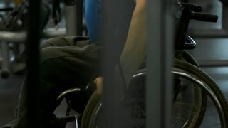 Tilt up with side view of focused paraplegic man in wheelchair doing chest fly exercise on cable machine in gym