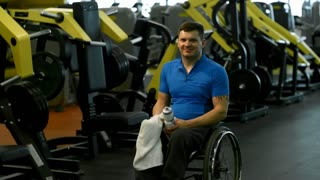 PAN of cheerful paraplegic man in wheelchair smiling and drinking from sports water bottle while posing in gym after tiring workout