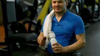 PAN of happy man in wheelchair drinking from sports water bottle and smiling for camera in gym after workout