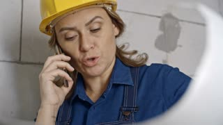 Mature female engineer wearing hard hat chatting on mobile phone and laughing while inspecting blueprints for construction project