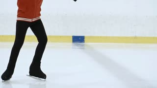 Amateur female figure skater performing spins on ice and explaining technique to little girl during personal workout