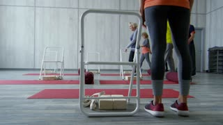 PAN with low-section of elderly people walking into fitness studio, then standing behind folding chairs and yoga mats before starting chair aerobics workout with unrecognizable female trainer