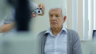 Tracking shot of senior man trying on lenses in trial frame with help of female eye doctor in ophthalmology clinic