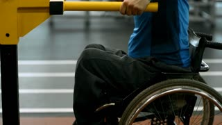 Tilt up of disabled man in wheelchair doing dips in gym