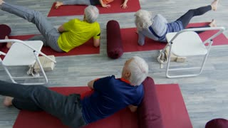 Tilt up of female fitness instructor and senior people lying on yoga mats and doing side leg lifts during pilates class