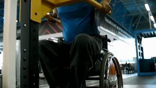Tilt up with low angle of focused paraplegic man in wheelchair breathing hard and doing dips exercise in gym