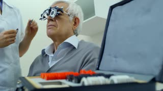 Low angled shot of female eye care professional inserting testing lenses into trial frame while checking eyesight of elderly man; senior patient talking to doctor and showing thumb up