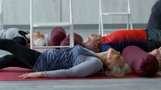 PAN with tilt up of female fitness instructor in sportswear talking and helping senior man lying on yoga mat with raised leg during group class
