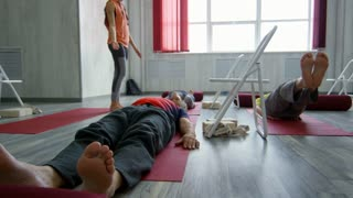 PAN of senior people lying on yoga mats and lifting their legs during fitness class with female instructor talking and helping elderly woman struggling to hold pose