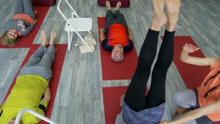 PAN with high angle of female instructor helping senior woman doing shoulder stand pose in group yoga class