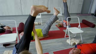 Tilt down of female yoga instructor helping elderly woman doing shoulder stand on mat; senior people lying with raised legs and holding pose