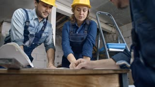 Tilt up of Asian builder and female construction worker wearing hard hats and overalls standing in unfinished building and discussing documents with foreman