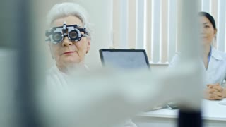 Smiling senior woman in trial frame sitting with female doctor at table in eye care clinic and looking at camera