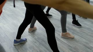 PAN with tilt up of elderly people in sportswear standing in line and trying to reach their toes while doing side bend exercise in yoga class