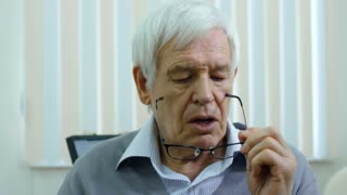 Senior man blowing on eyeglasses and wiping lenses with microfiber cloth in ophthalmology clinic