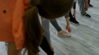 PAN of elderly people in sportswear standing in line and doing side bend exercise, then holding their balance during yoga class