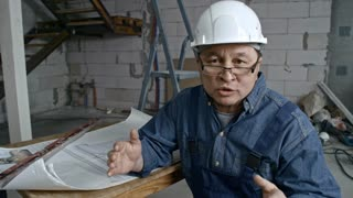 Medium shot of mature Asian engineer wearing glasses and hard hat sitting in unfinished building and explaining something while looking at camera