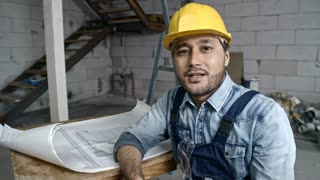 Medium shot of young Asian builder wearing hard hat and jeans overalls sitting in unfinished building and explaining how to draw layout plan before camera