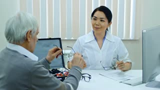 Smiling female eye care professional sitting at desk in clinic and helping senior patient to choose new eyeglasses