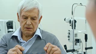 Tilt down of senior man speaking with ophthalmologist while choosing new eyeglasses in eye care clinic