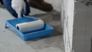 Tilt up with rack focus of male Asian worker in blue overalls painting brick wall with paint roller