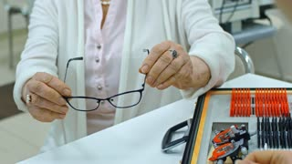 Tilt up of senior woman choosing new eyeglasses in eye care clinic and discussing them with ophthalmologist