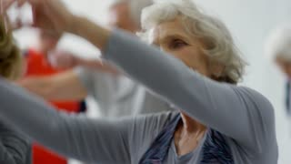 Handheld tracking shot of happy senior woman smiling and swinging raised arms during dynamic stretching group class