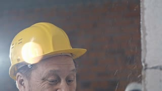 Tilt down of mature Asian construction worker in hard hat painting brick wall with paint roller