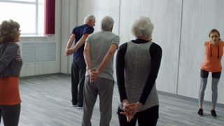 PAN of elderly people in sportswear repeating yoga pose after female teacher: they are slowly bending forward with their hands clasped behind their backs and stretching